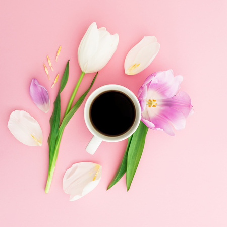 Summer composition with tulips, petals and mug of coffee on pink background. Flat lay, top view.