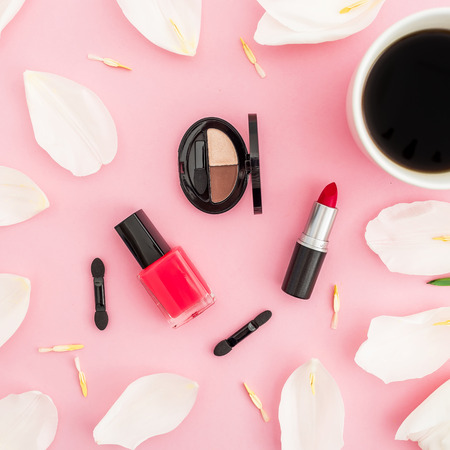 Beauty composition with tulips flowers, coffee cup and makeup cosmetics on pink background. Top view. Flat lay.