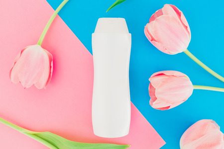 Shampoo bottle and tulips flowers on a pink and blue background. Flat lay, top view