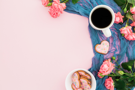 Holiday composition with roses, cookies and cup of coffee on pink background. Flat lay, top view