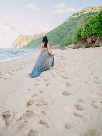 Brunette bride in blue wedding dress at the beach in Bali