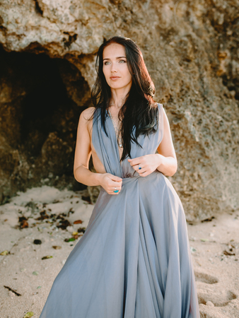 Portrait of a bride in a blue wedding dress at a beach with sunset or sunrise colors.