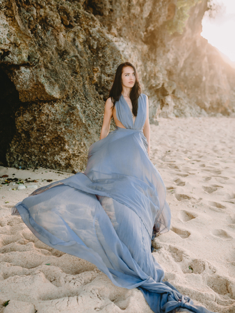 Portrait of brunette bride in blue wedding dress at beach with sunset colors.