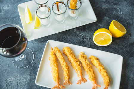 King prawn served with sauce and lemon. Sea food with glass of wine drink Standard-Bild