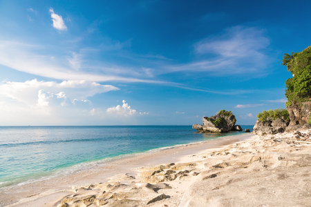 Tropical sand beach with rocks and blue ocean in Padang Padang