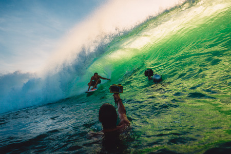 April 23, 2018. Bali, Indonesia. Surfer ride on a big barrel wave at Padang Padang. Professional surfing in ocean