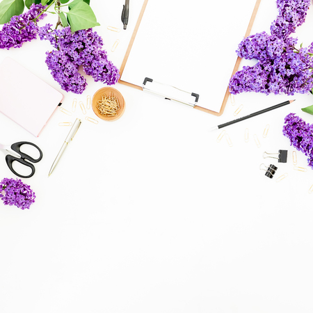 Copy space with clipboard, scissors, pen, lilac branches and accessories on white background. Flat lay, top view. Beauty blog concept with copy space. Stock Photo