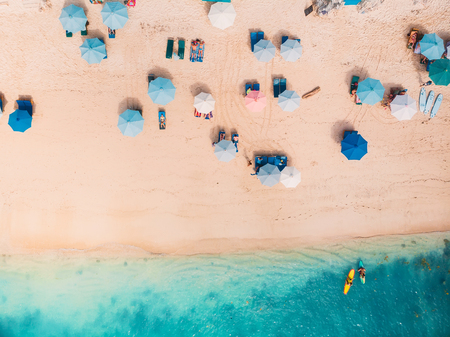 Vista superior de la playa de arena con agua de mar turquesa y coloridas sombrillas azules, toma aérea de drone