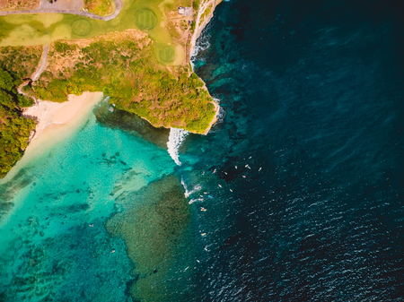 Tropical ocean with waves and surfers in Bali, drone shot. Aerial view. Stock Photo