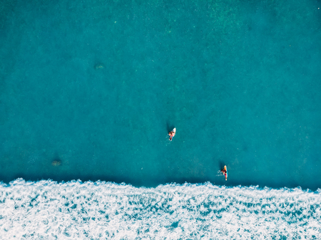 Aerial view of surfers and wave in tropical blue ocean. Top view