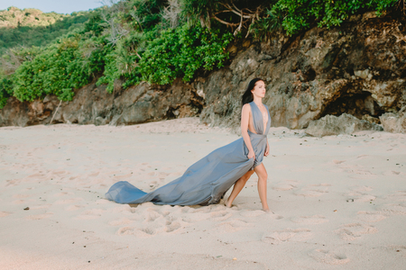 Attractive brunette bride in stylish blue dress at beach 免版税图像