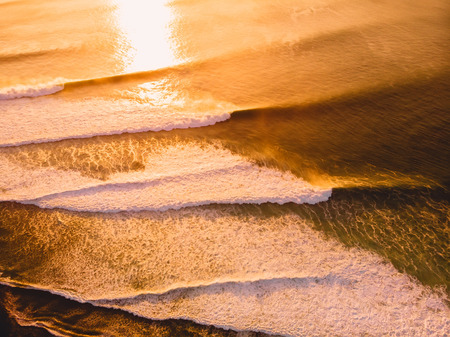 Aerial view of the big stormy waves at warm sunset
