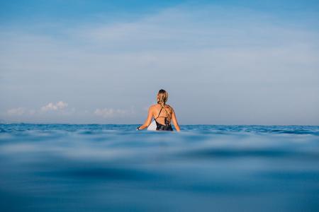 Alone surfer woman in swimwear with surfboard. Woman with surfboard in the ocean. Banco de Imagens