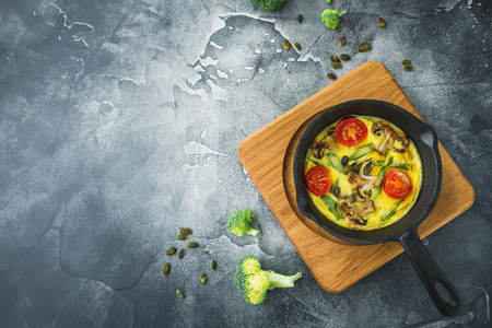 Healthy food of omelet in frying pan and pumpkin seeds. Flat lay, top view with copy space Stock Photo