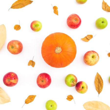 Thanksgiving autumn background with fall dried leaves, apple fruits and orange pumpkin on white background. Flat lay, top view