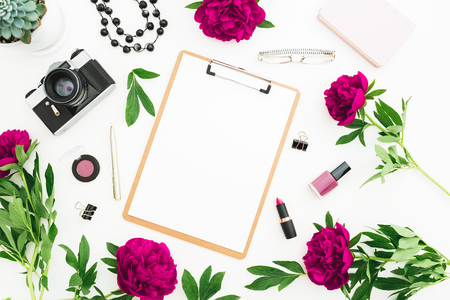 Freelancer workspace with clipboard, diary, peony flowers and retro camera on white background. Flat lay, top view. Beauty concept with copy space on clipboard