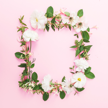 Frame of white flowers and leaves on a pink pastel background. Flat lay, top view. Floral pattern