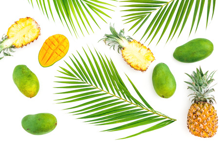 Tropic pattern of pineapple and mango fruits with palm leaves on white background. Flat lay, top view. Tropical concept. Stock Photo