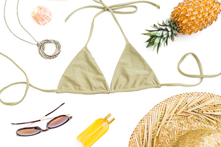 Tropical holiday concept. Pineapple fruits, sun glasses, straw hat and bikini swimwear on white background. Flat lay Stock Photo