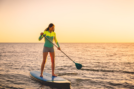 Attractive young woman at a stand up paddle board with sunset colors Stock Photo