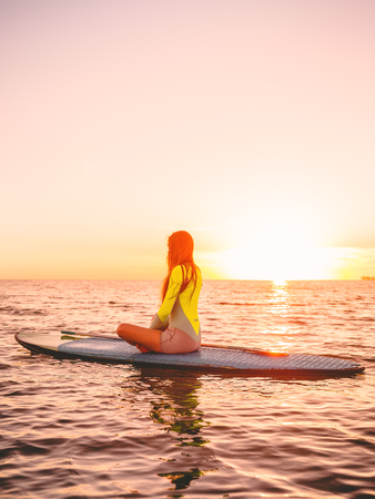 Stand up paddle boarding on a sea with warm sunset colors. Relaxing on ocean