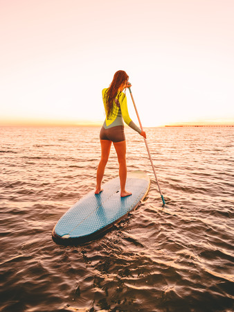 Sporty young woman at stand up paddle board with bright sunset colors