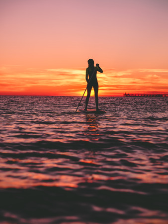 Sporty woman standing up paddle boarding on a flat warm sea with bright sunset Stock Photo