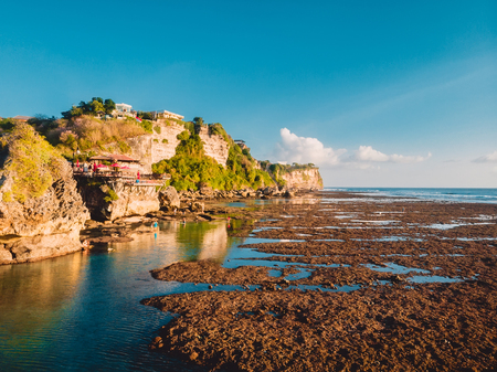 Aerial view of cliff, rocks and ocean at low tide in Bali