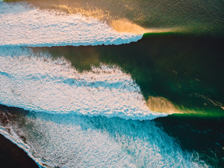 Aerial shooting of stormy waves at sunset. Biggest ocean wave