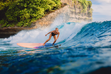 Surfer woman ride on wave surfing. Surfer and ocean wave in Bali Stock Photo