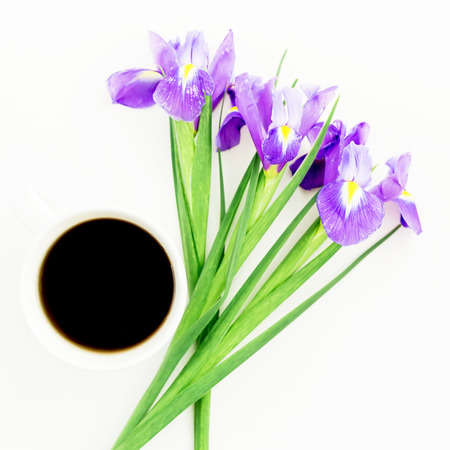 Bouquet of Iris flowers with mug of black coffee on white background. Flat lay, Top view.