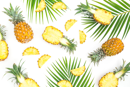 Tropic pattern of pineapple with palm leaves on white background. Flat lay, top view. Tropical concept.