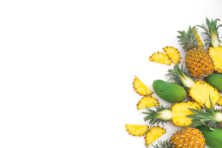 Frits background of pineapple and mango fruits on white background. Flat lay, top view. Copy space