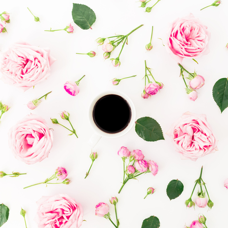 Pink rose flowers with mug of black coffee on white background. Flat lay, Top view. Flowers texture.