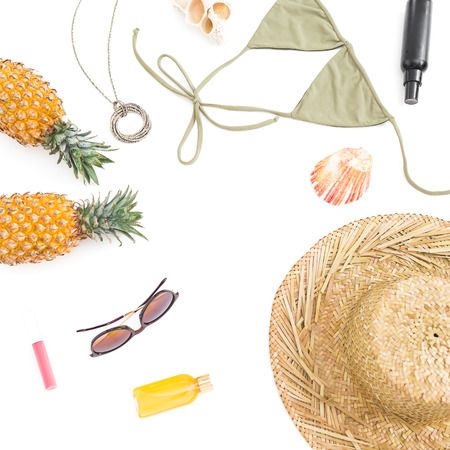 Summer tropical concept. Pineapple fruits, sun glasses, hat and swimwear on white background. Flat lay, top view. Copy space.