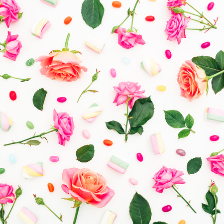 Pink or orange roses flowers and marshmallow with colorful candy on white background. Flat lay, top view. Holidays background
