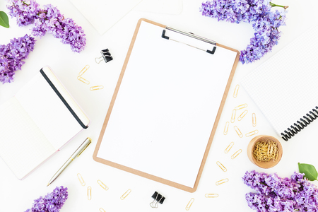 Workplace composition with clipboard, diary, branches of lilac flowers and accessories on white background. Flat lay, top view.