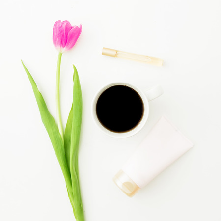 Pink flower with mug of black coffee and cosmetics on white background. Flat lay, Top view.