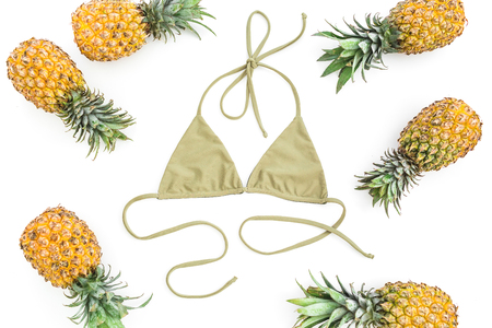 Beach concept. Pineapples fruits and swimwear on white background. Flat lay, top view.