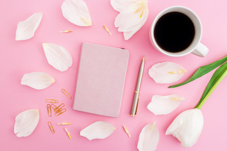 White flowers and petals with coffee mug, notebook and pen on pink background. Blogger concept. Flat lay, top view. Stock Photo