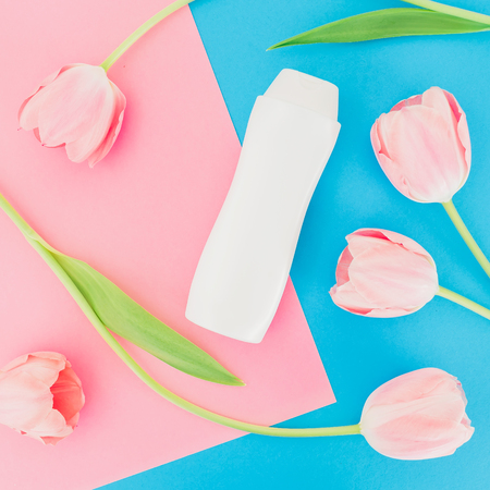 Shampoo bottle and tulips flowers on a pink and blue background. Flat lay, top view. Beauty concept Stock Photo