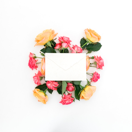 Paper card with red and orange roses and leaves on white background. Flat lay, top view. Beauty concept Stock Photo