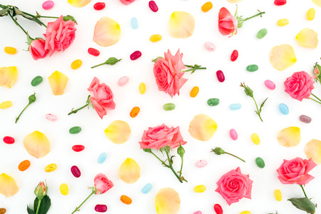 Roses flowers and petals with bright sugar candy on white background. Flat lay, top view.