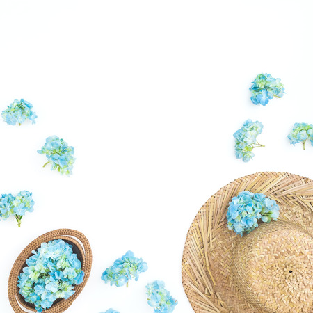 Blue hydrangea flowers with straw hat on white background. Flat lay, top view. Floral background Stock Photo