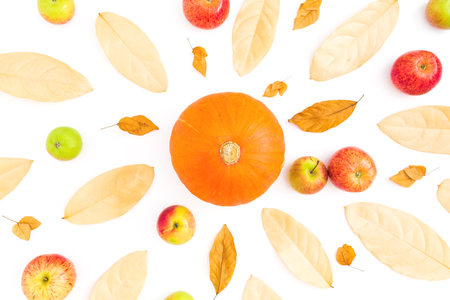 Autumn background with fall dried leaves, apples and pumpkin on white background. Flat lay, top view
