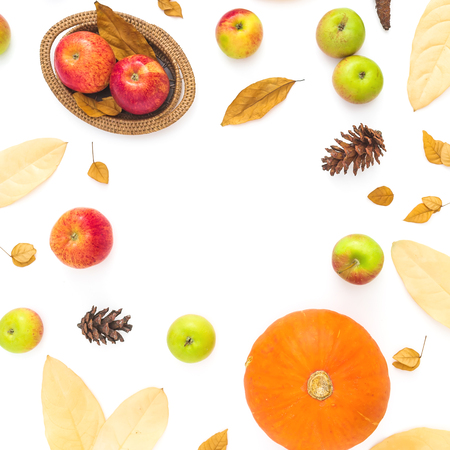 Autumn frame made of fall leaves, pine cones, apples and pumpkin on white background. Thanksgiving day. Flat lay, top view