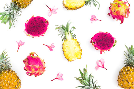 Fruit background of pineapple and dragon fruits with tropical pink flowers on white background. Flat lay, top view.