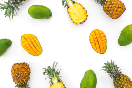 Fruit background of pineapple and mango fruits on white background. Flat lay, top view. Tropical concept. Stock Photo