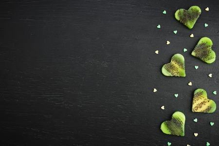 Slice of kiwi fruit on black background. Flat lay, top view. Heart symbol of fruits