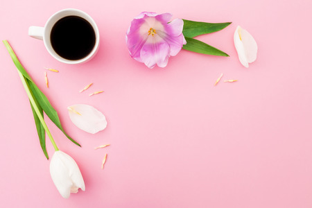Composition with flowers, petals and mug of coffee on pink background. Frame background. Flat lay, top view.